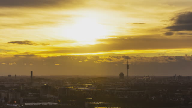 T/L ZOOM vibrant cloudy sunset above Munich's skyline with the sun setting behind the television tower in Olympia Park