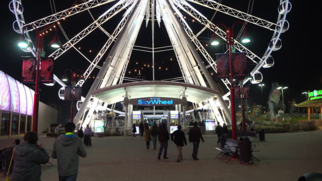 vidéos et rushes de vibrant colors of the skywheel during the blue hour the main plaza full of recreational options surrounds the tourist attraction that is the ferry... - attraction foraine équipement de loisirs