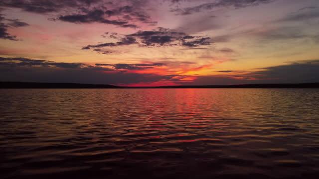 stockvideo's en b-roll-footage met vibrant dark red sunset dusk sky clouds flying over water aerial view - breed