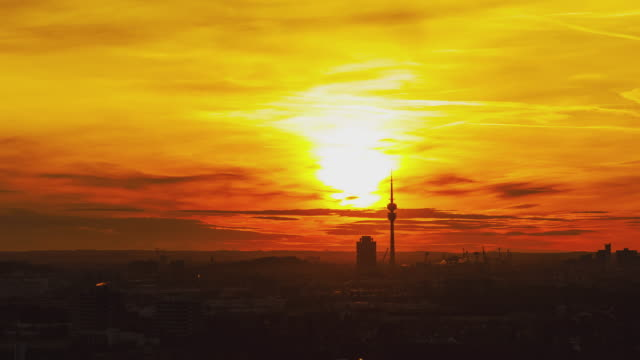"""T/L vibrant day to night transition with the sun setting behind Munich's iconic television tower in """"Olympiapark"""" and BMW's iconic building the """"Zylinder"""""""