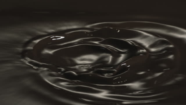 a vibrant ripple in dark liquid chocolate. - high speed photography stock videos & royalty-free footage