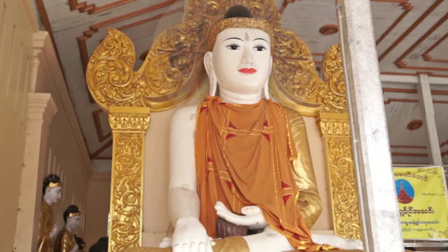 a vibrant statue of a religious figure in a monestary in yangon, myanmar - male likeness stock videos & royalty-free footage