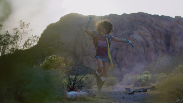 vidéos et rushes de slo mo. vibrant young woman dances in a cloud of dust in a wild desert landscape. - tatouage