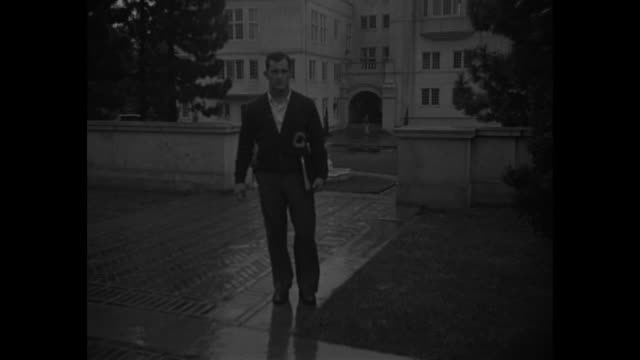 Vic Bottari in civilian clothes walking on University of California campus towards camera he stops and poses for photo opportunity / Bottari walking...