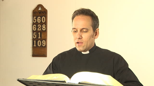 vicar / priest reading the bible - hd & pal - priest stock videos and b-roll footage