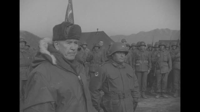 Vice President Alben Barkley wearing a cap and heavy fur lined parka as Gen Matthew Ridgway watches / pan right of Barley receiving salute from...