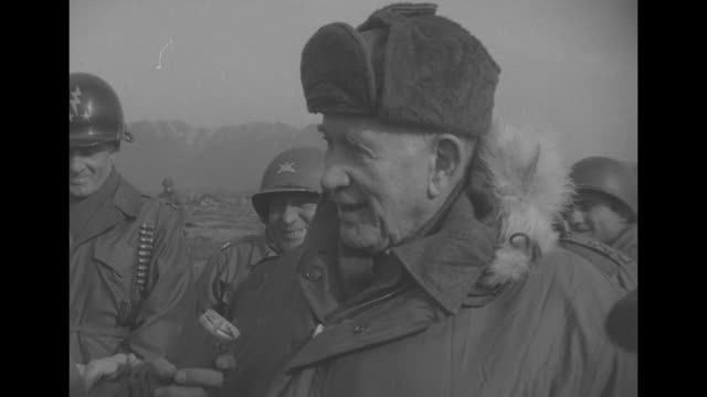 Vice President Alben Barkley wearing a heavy fur lined parka is saluted by a soldier as General Matthew Ridgway looks on / Barkley and Ridgway walk...