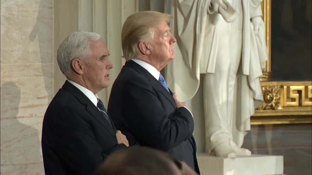 Vice President Mike Pence and President Donald Trump hold their hands over their hearts at a ceremony where Bob Dole was awarded the Congressional...