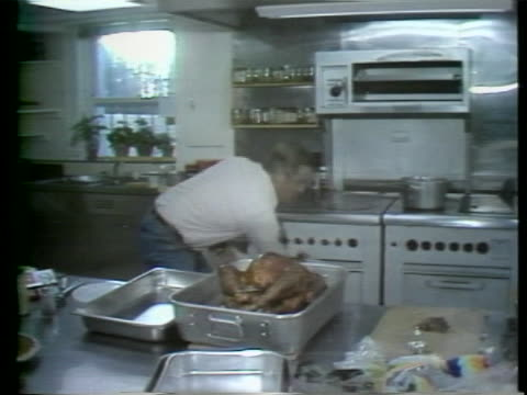 vice president walter mondale takes thanksgiving turkey out of oven. there is a medium shot of vice president walter mondale reaching into an oven.... - thanksgiving politics stock videos & royalty-free footage