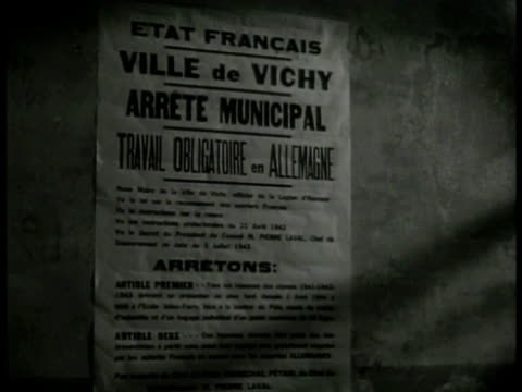 vidéos et rushes de vichy poster on wall saying that work in germany is mandatory male ripping poster down writing on wall: 'v' w/ cross of lorraine in center 'vive de... - seconde guerre mondiale
