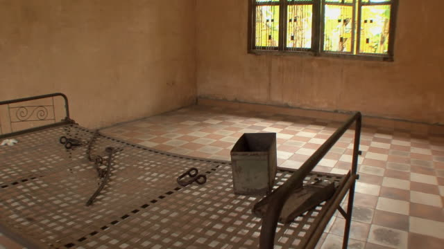 cu pan victim's bed with torture instruments in cell in tuol sleng school, phnom penh, cambodia - torture stock videos & royalty-free footage