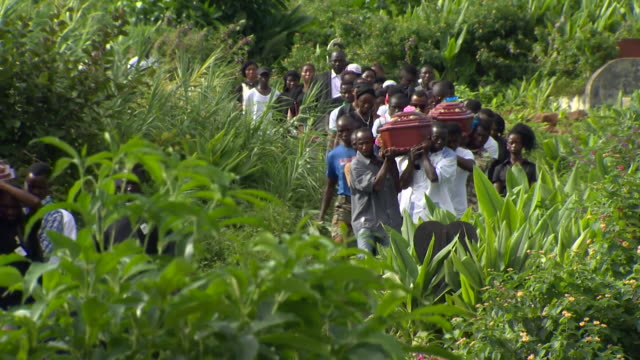 Victims of a devastating landslide in Sierra Leone being buried