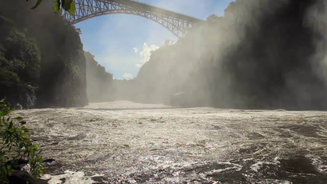 victoria falls bridge with water and spray below - victoria falls stock videos and b-roll footage
