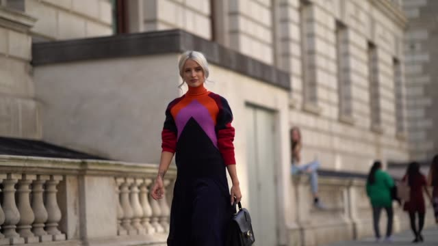 stockvideo's en b-roll-footage met victoria magrath wears an orange red and pink wool pullover with a turtleneck a black lace pleated skirt a black leather bag during london fashion... - modeweek