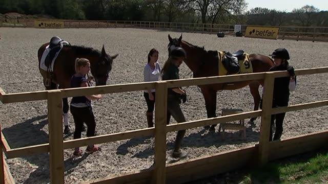 victoria pendleton trains as jump jockey; england: buckinghamshire: high wycombe: ext long shot of horses being walked around paddock/ horses in... - jockey stock videos & royalty-free footage