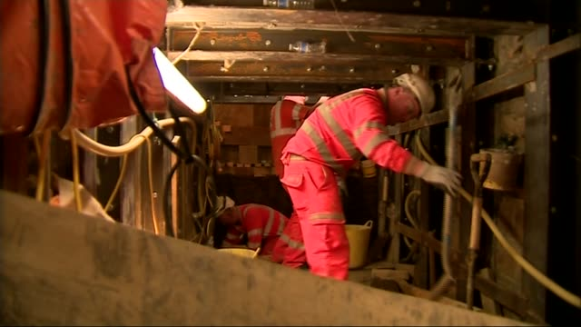 vídeos de stock, filmes e b-roll de redevelopment of tube station continues back view construction worker along tunnel david smith interview sot construction workers in tunnel general... - tunnel