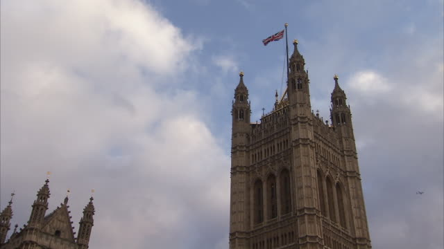 Victoria Tower stands against a cloudy blue sky at the Palace of Westminster in London. Available in HD.