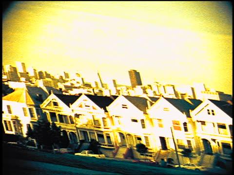 vídeos de stock e filmes b-roll de distorted victorian houses on steiner street with skyline in background / san francisco - super exposto