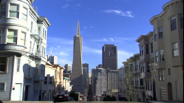 Victorian houses stand in front of the Transamerica Pyramid.