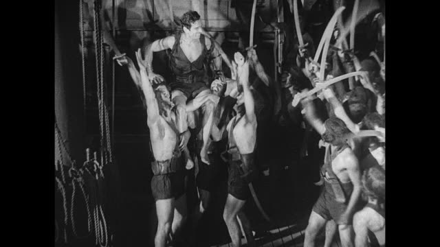 victorious pirate (douglas fairbanks)is celebrated as he is pulled to the top of the ship - 無声映画点の映像素材/bロール