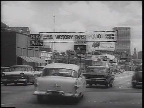 """victory over polio"""" banner over town street with traffic / texas / newsreel - polio stock videos & royalty-free footage"""