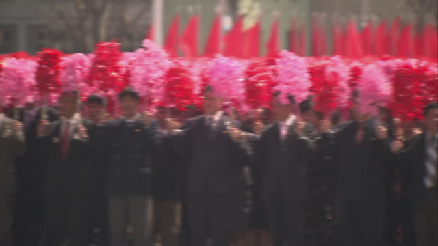 victory parade in kim iisung square in pyongyang north korea with well dressed men shaking flower pom poms - pom pom stock videos & royalty-free footage