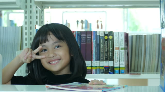 victory sign by asian girl in library - child waving stock videos & royalty-free footage