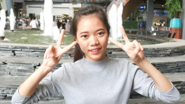 stockvideo's en b-roll-footage met teken van overwinning, handgebaar door jonge vrouw - zwaaien gebaren