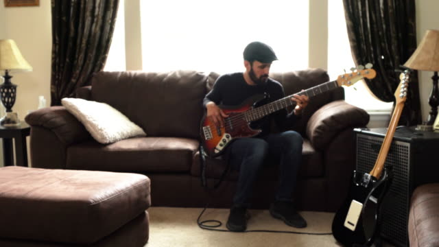a videa clip of a talented young man practicing his bass guitar in his living room - amplifier stock-videos und b-roll-filmmaterial