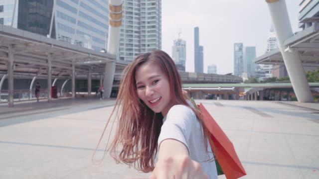 Video 4k: junge Frau zieht ihren Freund durch Stadt, glückliche Freundin macht ihr Mann zu ihr in den Warenkorb zu folgen.