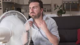 Video about man refreshing in front of air electric fan
