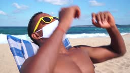 4K Video Afro couple wearing protective face mask on the beach and having summer vacation,during COVID-19
