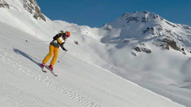 4k video alpine skiing woman in wide turns on ski slope on sunny day - ski holiday stock videos & royalty-free footage