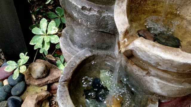 Video and audio of water fountain in garden.
