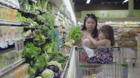 vídeos y material grabado en eventos de stock de video asiático materno-infantil de las compras de comestibles. - bolsa de plástico