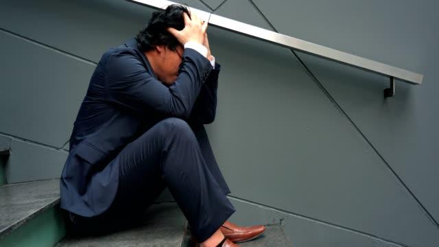 4 k ビデオ: アジアの無職の男を強調しました。大人の不安ありますうつ病や問題にドラッグを生活感悲しみ、孤独、心配に。 - 心配する点の映像素材/bロール