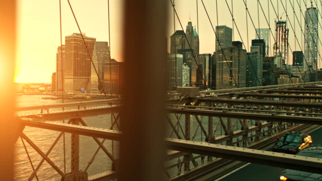 stockvideo's en b-roll-footage met video bij zonsondergang in brooklyn bridge tegen verlichte skyline - pannen
