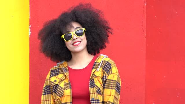 vidéos et rushes de vidéo 4k belle femme afro-américaine aux cheveux afro, lunettes de soleil jaunes et vêtements colorés sourit sur fond bleu - femme de pouvoir