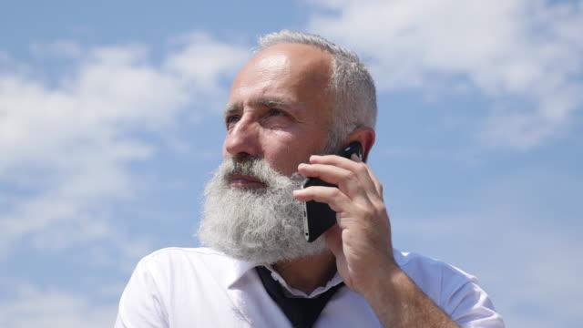 4K Video - Geschäft. Ein bärtiger senior Geschäftsmann spricht am Telefon.