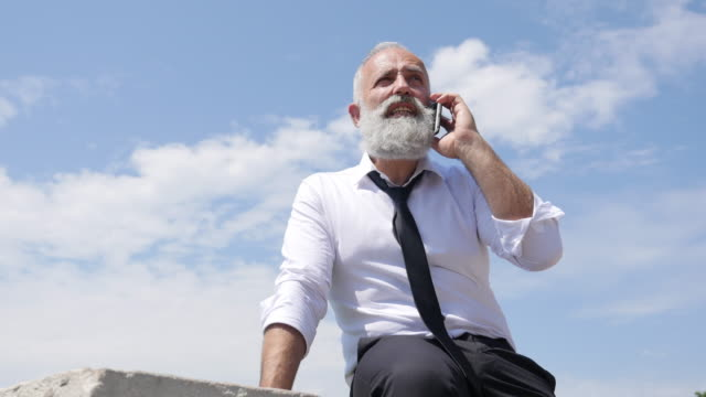 4k video - business. a bearded senior businessman  speaks on the phone. - shirt and tie stock videos & royalty-free footage