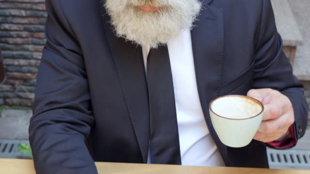 vídeos de stock, filmes e b-roll de vídeo de 4k - business.  empresário barbudo é usando um telefone e tomando café - 50 59 years