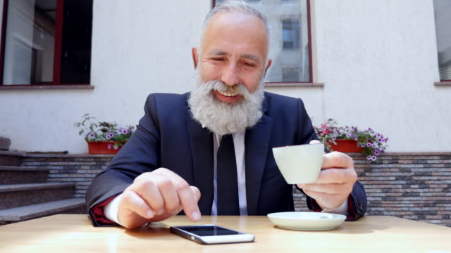 4k video - business.  bearded businessman is using a phone and drinking coffee - 50 59 years video stock e b–roll