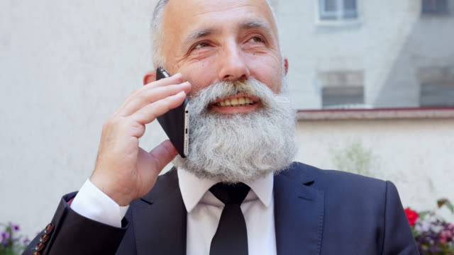 4k video - business. bearded businessman talking on the phone and drinking coffee - 50 59 years video stock e b–roll