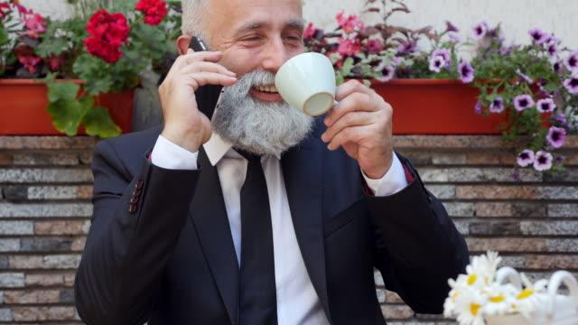 vídeos de stock, filmes e b-roll de vídeo de 4k - business. empresário barbudo falando ao telefone e tomando café - 50 59 years