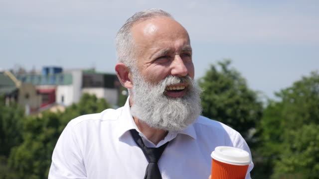 4k video - business. bearded senior businessman drinks coffee - shirt and tie stock videos & royalty-free footage
