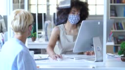 4K Video  Business people separated by an acrylic glass for social distancing, wearing protective face mask and discussing advisor concept , during COVID-19