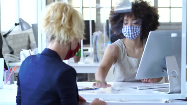 vídeos de stock e filmes b-roll de 4k video  business people separated by an acrylic glass for social distancing, wearing protective face mask and discussing advisor concept , during covid-19 - cliente
