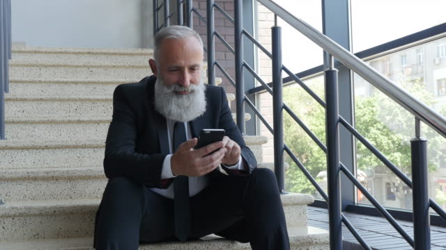 4k video - business. senior businessman sitting on stairs with smartphone - 50 59 years video stock e b–roll