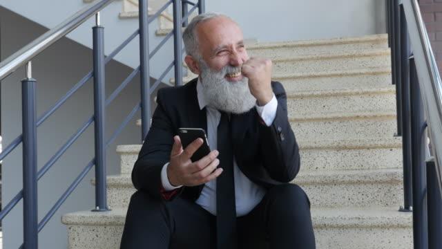 4k video - geschäft. leitenden geschäftsmann sitzt auf der treppe mit smartphone - treppe stock-videos und b-roll-filmmaterial