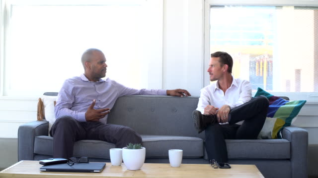 4k video - business - two men on the couch - cross legged stock videos & royalty-free footage